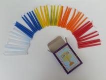 Buntes Hannukah leuchtet die Schaffung der Form eines Regenbogens mit einem Zeichen einer Lampe auf dem offenen Kerzenkasten durc Stockbild