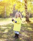 Buntes Herbstfoto, kleines Kind, das Spaß hat Lizenzfreie Stockfotografie