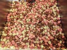 Buntes Karamell, Schokolade, rosa Kuchen und Vanillepopcorn - Popcorn innerhalb einer gestreiften Tasche stockfoto