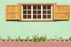 Buntes karibisches Fenster und Fensterläden in einer grünen Wand II Lizenzfreies Stockbild