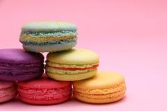 Buntes Kuchenmacaron oder -makrone der Nahaufnahme auf rosa Hintergrund von der Vorderansicht, buntes Mandelgebäck, Pastellfarben lizenzfreies stockfoto