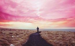Buntes landschaftlich gestaltet, ein Mann, der allein auf dem Weg vorwärts mit buntem Himmel geht stockfotografie