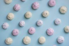 Buntes Lebensmittelmuster von rosa, gelben und weißen Meringen auf blauem Hintergrund stockfotografie