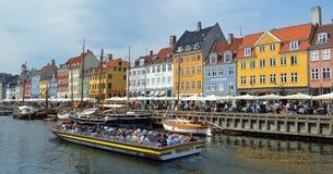 Buntes Nyhavn und touristisches Boot stockbild