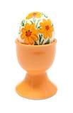 Buntes Osterei in der orange Schale. Lokalisiert auf weißem Hintergrund Stockfotografie