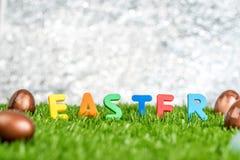 Buntes Ostern-Wort und -kaninchen stempeln auf Eiern auf grünes Gras fie Stockfoto