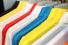 buntes Polohemd auf einem Aufhänger Lizenzfreie Stockbilder