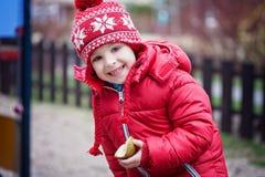 Buntes Porträt des netten kleinen Jungen, Birne auf dem playgro essend Stockfoto