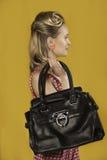Buntes Porträt eines Retro- Pin-up-Girl mit einer schwarzen Lederhandtasche Stockfotos