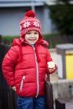 Buntes Porträt des netten kleinen Jungen, Birne auf dem playgro essend Stockbild