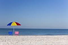 Buntes Regenschirm, rosafarbenes u. Blaues Deckchairs auf Strand Lizenzfreie Stockfotos