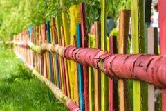 Buntes rotes gelbes blaues Grün malte hölzernen Zaun Stockfoto