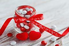 Buntes Süßigkeitsglas verziert mit einem roten Bogen mit Herzen auf weißem hölzernem Hintergrund Roter heart-shaped Schmucksacheg Lizenzfreie Stockbilder