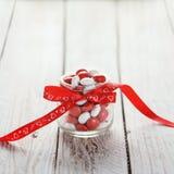 Buntes Süßigkeitsglas verziert mit einem roten Bogen mit Herzen auf weißem hölzernem Hintergrund Roter heart-shaped Schmucksacheg Lizenzfreies Stockfoto