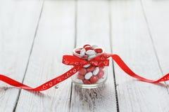Buntes Süßigkeitsglas verziert mit einem roten Bogen mit Herzen auf weißem hölzernem Hintergrund Roter heart-shaped Schmucksacheg Stockbild
