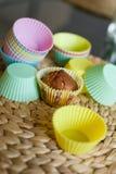 Buntes Silikon formt für backende kleine Kuchen und Muffins auf einer Strohtabellenmatte Lizenzfreie Stockbilder