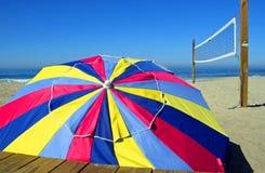 Buntes Strandschirm-und Volleyball-Netz Stockfotografie