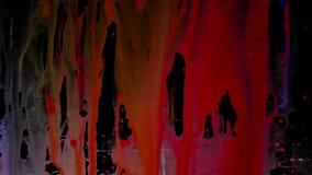 Buntes Tintentröpfchendia auf Glas Schwarzer Hintergrund Stockbilder