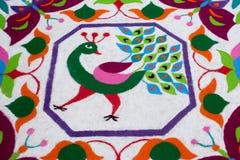 Buntes traditionelles Blumenmuster Rangoli gemacht mit trockenen pulverisierten Farben mit Pfau, Blumen und Schmetterlingen Lizenzfreies Stockbild