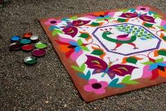 Buntes traditionelles Blumenmuster Rangoli gemacht mit trockenen pulverisierten Farben mit Pfau, Blumen und Schmetterlingen Lizenzfreie Stockfotos