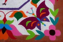 Buntes traditionelles Blumenmuster Rangoli gemacht mit trockenen pulverisierten Farben mit Pfau, Blumen und Schmetterlingen Stockfotografie