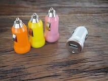Buntes USB-Auto-Ladegerät auf einem hölzernen Brett mit Technologie- und Energiekonzept Lizenzfreie Stockfotografie