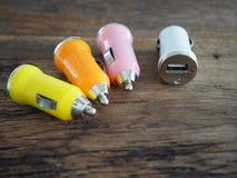 Buntes USB-Auto-Ladegerät auf einem hölzernen Brett mit Technologie- und Energiekonzept Lizenzfreie Stockbilder