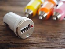 Buntes USB-Auto-Ladegerät auf einem hölzernen Brett mit Technologie- und Energiekonzept Stockbild
