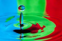 Buntes Wassertröpfchen des abstrakten Hintergrundes, das Spritzen macht Stockfotografie