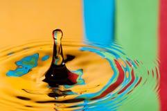 Buntes Wassertröpfchen des abstrakten Hintergrundes, das Spritzen macht Stockbild