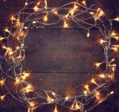 Buntes Weihnachtsbeleuchtet warme Goldgirlande auf hölzernem rustikalem Hintergrund Gefiltertes Bild Lizenzfreie Stockfotos