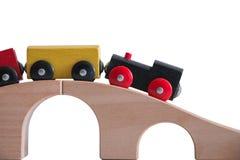 Buntes Zugspielzeug auf Holzbrücke mit weißem Hintergrund Lizenzfreies Stockbild