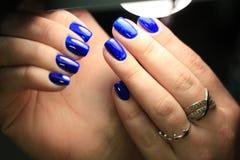 Buntglas-Gelpolitur der Maniküre blaue mit einem Bild lizenzfreie stockfotografie