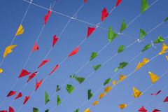 Bunting, colorful party flags, on a blue sky. Stock Photos