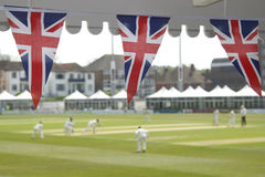 Bunting and cricket. Union Jack flags flutter at a cricket pavilion while the action goes on Royalty Free Stock Photos