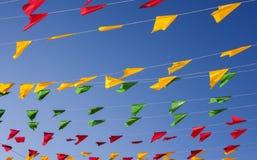Bunting färgrika partiflaggor, på en blå himmel royaltyfri fotografi