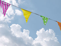 Bunting, flags photographed over blue sky, clouds coming in. Royalty Free Stock Image