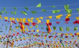 Bunting, kleurrijke partijvlaggen, op een blauwe hemel stock afbeelding