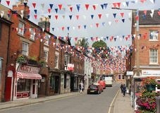 Bunting and shops, Dig St., Ashbourne, Derbyshire. View looking along Dig Street towards Church Street in Ashbourne, Derbyshire, England. The street has red royalty free stock image