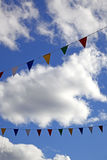 Bunting sky 1. Colourful bunting flying in the wind on a sunny day with a blue sky ad white clouds. With space for text Stock Images