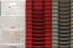 Buntlagring av nya färgglade vita, gråa och röda spjällådor för plast- behållare royaltyfri foto