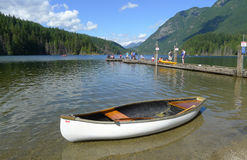 Buntzen Lake Park with a White Canoe at the Front. Buntzen Lake Park in Anmore, BC, Canada. People are fishing and canoeing royalty free stock images