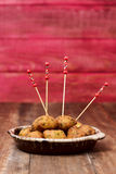 Bunuelos de bacalao, spanish cod fritters. Some bunuelos de bacalao, spanish cod fritters, served as tapas in a earthenware plate, on a rustic wooden table stock image