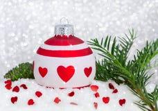 Buon anno della cartolina di Natale con la bagattella, i cuori, l'albero, la neve, il cono e il bokeh bianchi rossi Immagine Stock Libera da Diritti