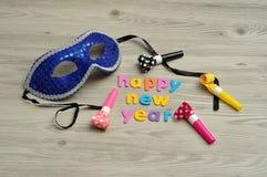 Buon anno nelle lettere variopinte con una maschera ed i ventilatori del partito Fotografie Stock