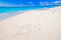 Buon anno scritto sulla sabbia bianca della spiaggia con Immagine Stock