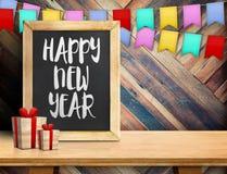 Buon anno sulla lavagna con il regalo e l'insegna variopinta della bandiera Fotografia Stock Libera da Diritti