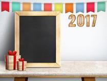 Buon anno sulla lavagna con il regalo e l'insegna variopinta della bandiera Immagini Stock