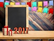 Buon anno sulla lavagna con il regalo e l'insegna variopinta della bandiera Fotografie Stock