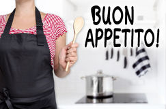 Buon appetito cook holding wooden spoon background Stock Image